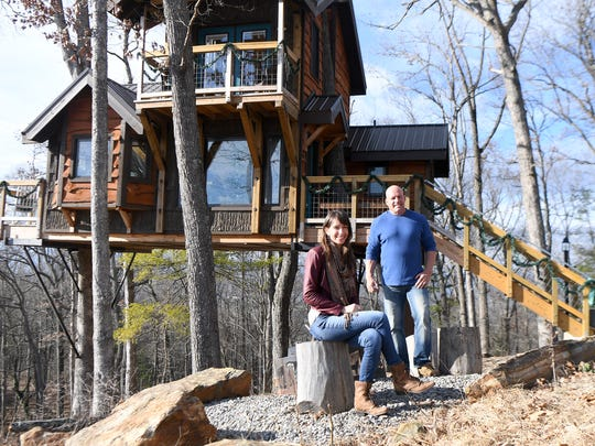 Serenity treehouse manager Nicolette Baglio of Motley Hospitality Co. and owner Mike Parrish pose in front of the house supported entirely by trees in Woodfin. They said that they think the treehouse is the only one in Western North Carolina supported entirely by trees with a certificate of occupancy.