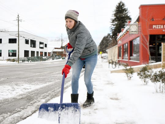 Sarah Coogan scrapes the sidewalk in front of her business,
