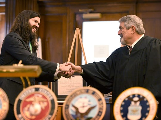 Buncombe County Veterans Treatment Court coordinator Kevin Rumley shakes hands with Judge Marvin Pope after he was presented with a frame containing his Purple Heart during a graduation ceremony for the program at the Buncombe County Courthouse on Friday, Jan. 19, 2018. Rumley's Purple Heart which he once presented to Judge Pope will be displayed for others going through the program to see.