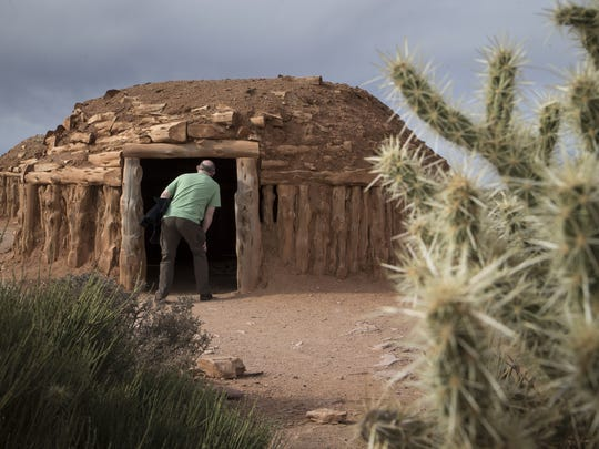 A visitor views the inside of a hogan in the Native