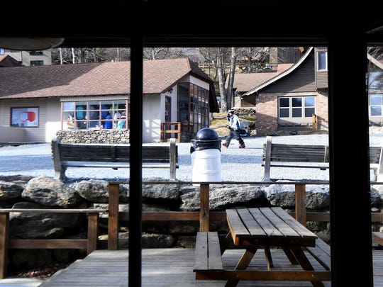 A skier seen through the windows of the Beech Mountain Brewing Company walks through the village at Beech Mountain Resort in Beech Mountain on Friday, Jan. 26, 2018.