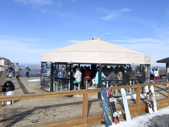 Skier enjoy a drink and the view at the 5506' Sky Bar