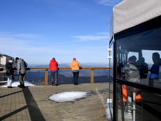 Skiers enjoy a drink and the view at the 5506' Sky