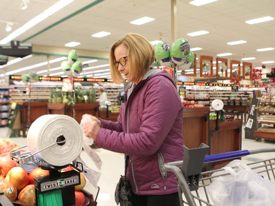 The Glenway Ave. Kroger is using an optional scanner system called Scan, Bag, Go to help shoppers get in and out faster. Alex Campbell, 25, shops using the scanner. Andrea Cornett, 63, grabs some apples that she scanned.