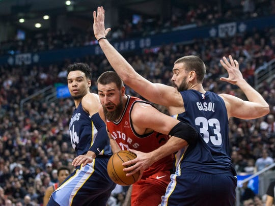 Raptors center Jonas Valanciunas (17) looks to lay off a pass despite pressure from Grizzlies center Marc Gasol (33) and forward Dillon Brooks on Feb. 4, 2018. Valanciunas is headed for Memphis in a trade that will take Gasol to Toronto.