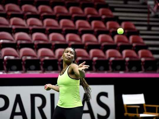 Venus Williams practices on the court with her sister,