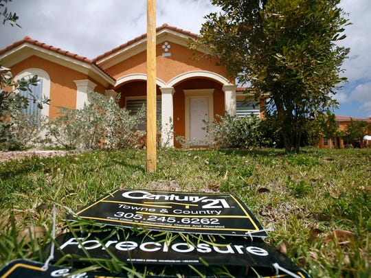 In this March 24, 2009 photo, a for sale sign lays on the ground in front of a foreclosed home in Homestead.