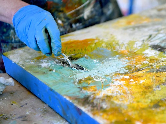 Cindy Walton scrapes layers of paint off a piece to reveal different colors underneath as she works on a piece at her studio in The Wedge Studios building on Thursday, Feb. 8, 2018. Walton uses layers of oil paint with cold wax medium and pigment sticks to create layers of color and texture in her works.