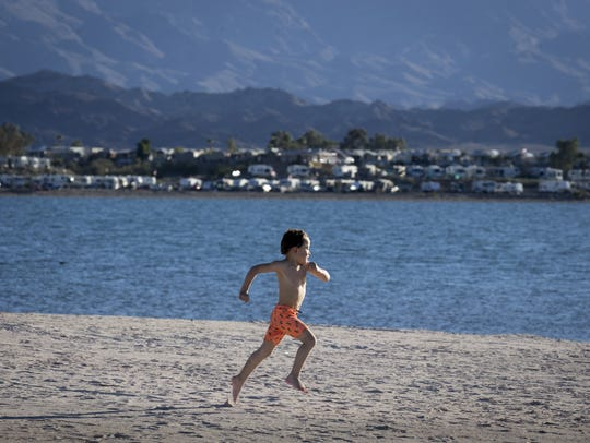 Tristan Harrington (5) runs along the beach, Febuary