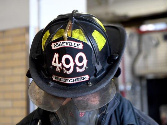 Matthew Kaylor demonstrates how much gear a firefighter