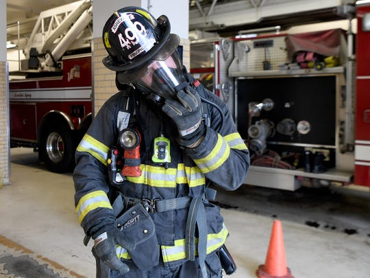 Matthew Kaylor connects his oxygen tank to his mask as he demonstrates how much gear a firefighter wears when called out to a fire. For years firefighters have been making efforts to protect their lungs from the carcinogens in smoke but only recently have started worrying about exposure through their skin and contaminated gear.