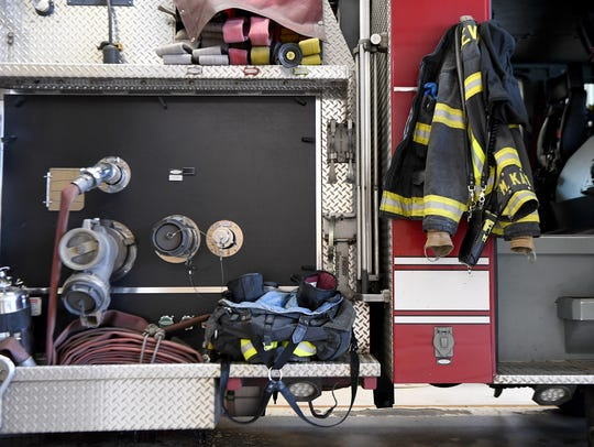 A firefighter's turnout gear sits on one of the trucks