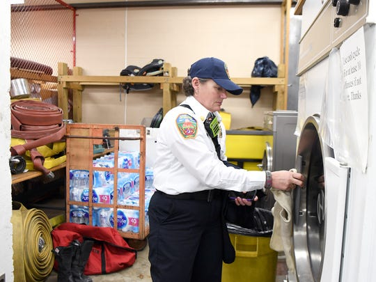 Asheville Fire Department Division Chief Joy Ponder pulls a mask out of a heavy-duty dryer, known as the extractor, at the Asheville Police Department that can be used to wash firefighters turnout gear. Firefighters used to only wash their gear once or twice a year, wearing dirty gear as a badge of honor.