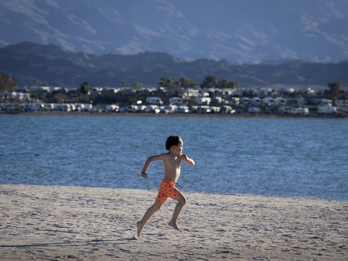 Tristan Harrington (5) runs along the beach, February