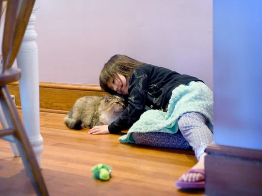 Gemma Glovan, 5, cuddles with Petrie the cat during