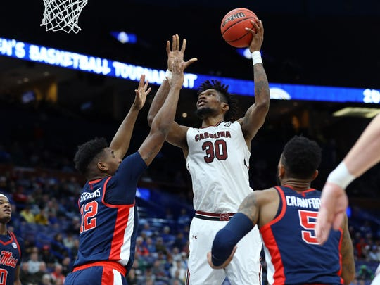 South Carolina Gamecocks forward Chris Silva (30) puts up a shot in the lane as he is challenged by Mississippi Rebels forward Bruce Stevens (12) during the second half of the first round of the SEC Conference Tournament at Scottrade Center. South Carolina won 85-84. Mandatory Credit: Billy Hurst-USA TODAY Sports