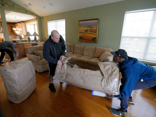 Chris Biskey and Rasheed Hamsford, both of Jackson and movers with Freehold Movers, wrap a piece of furniture with plastic as Tom Gatti, the founder of the Senior Action Group in Lakewood and one of the most vocal figures in the opposition to township growth, and his wife, Ellen Gatti, move out of their Lakewood home after 12 years in Lakewood, NJ Monday, March 12, 2018.