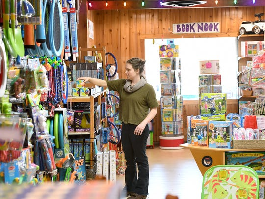 Madeline Owen arranges items on shelves at Dancing Bear Toys in Asheville on Thursday, March 15, 2018. The store has a wide variety of toys and displays that allow children, and adults, to give many of them while visiting the store.