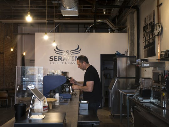 Damian Serafine makes a flat white at his new coffee