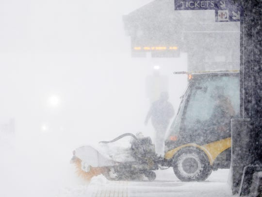 A worker tries to clear snow and ice from the Metro
