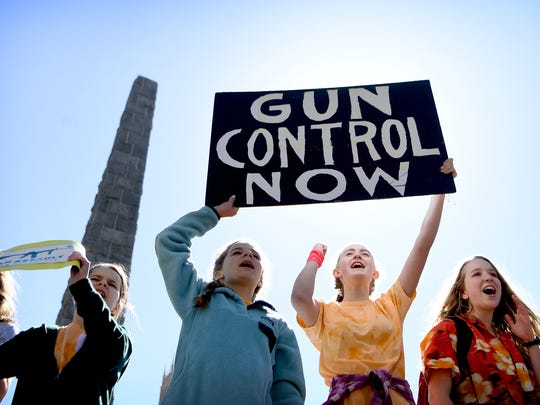 """Hangar Hall School for Girls seventh grade students Aleah Seay, 13, and McKenzie Sills, 12, hold a sign reading """"Gun Control Now"""" at the Vance Monument during a national school walkout for gun reform on Friday, April 20, 2018."""
