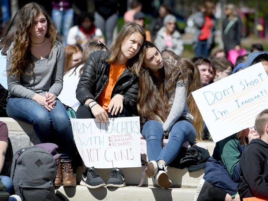 Claire Burnet, 17, a junior at Asheville High School, left, and Ingrid Kalwitz, 17, a junior at SILSA, listen to speakers during a national school walkout for gun reform at Pack Square Park on Friday, April 20, 2018.