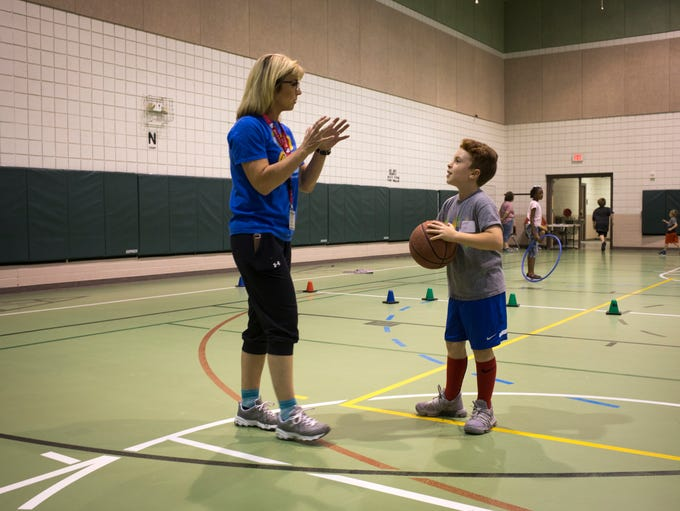 Second-grader Carter Upham plays basketball with volunteer