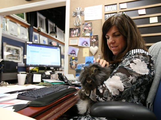 Emily Scotto, project manager, pets Shiloh, the office bunny, at her desk at Creative Displays & Design in Tinton Falls, NJ Thursday April 26, 2018.