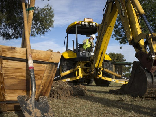 Jonathon Wells operates a backhoe while digging a hole to plant a tree in at Cortez Park in Phoenix.