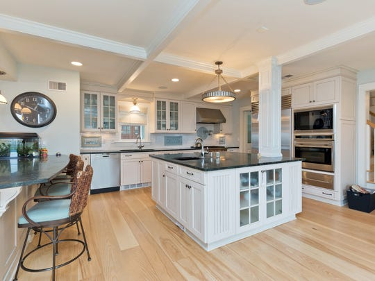 The all-white kitchen features custom cabinetry and stainless steel appliances.