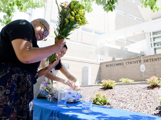 Maya Avery, with Southerners on New Ground, arranges flowers outside of the Buncombe County Detention Center as the group prepares to bail women out of the jail so they will be home for Mother's Day during the Black Mamas Bailout on Friday, May 11, 2018.