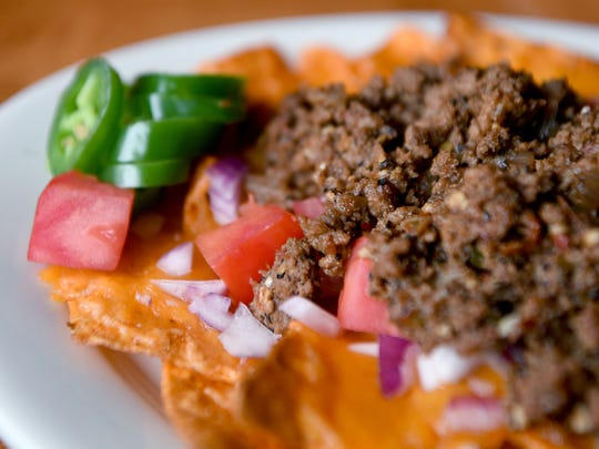Doritos nachos at The Barrelhouse in North Asheville are nacho cheese Doritos topped with seasoned ground beef, cheddar cheese, onions, tomatoes and jalapeno and served with sour cream.