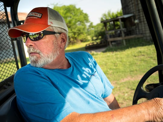 Bob Strasser drives out to feed the cattle at his farm,