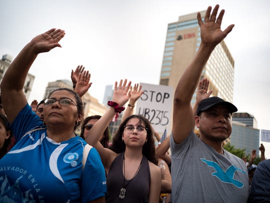 Kenya Martinez, center, of Gallatin, Tenn., holds her hand up during a protest against HB 2315, a bill that would ban sanctuary cities in Tennessee and require local law enforcement detain certain immigrants, at Public Square Park in Nashville, Tenn., Wednesday, May 16, 2018.
