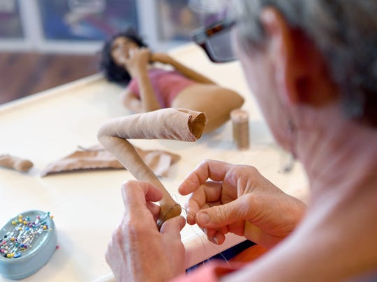 Ann Hord-Heatherley sews a foot onto a leg as she works in her studio at her home in Weaverville on Friday, May 28, 2018.
