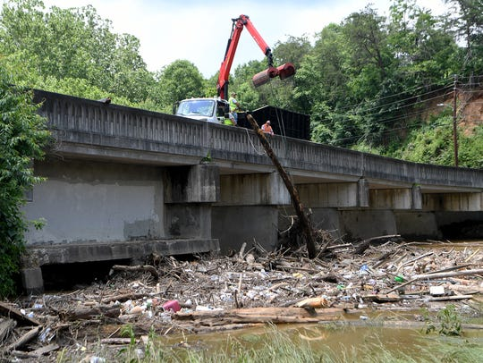 A City of Asheville crew works to remove debris from