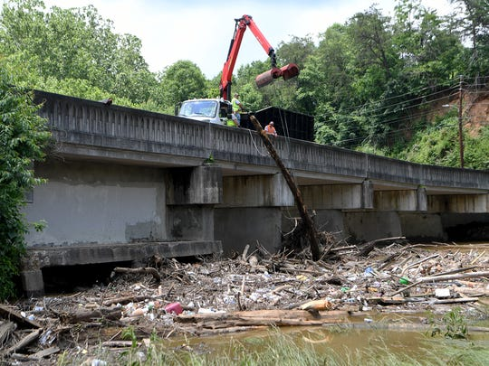 A City of Asheville crew works to remove debris from the former dam at Recreation Park on Thursday, May 31, 2018.