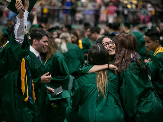 Graduates hug following the Douglas McKay High School