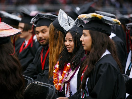 Graduates listen as Principal Sara LeRoy speaks during