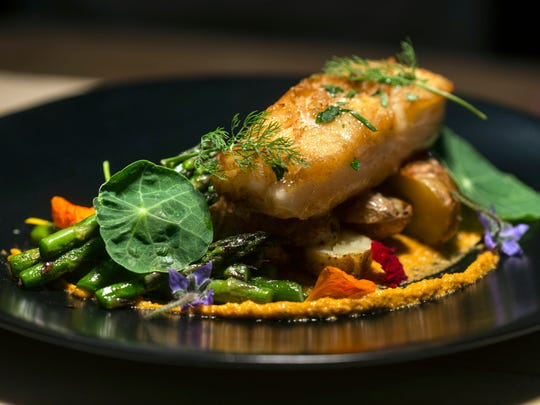 The pan seared fish with gochujang romesco and bourbon brown butter at MilkWood is served with a splash of colorful garnishing. 5/31/18