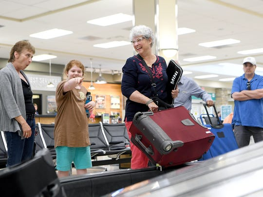 Wendy Haner, of Asheville, picks up her bag after arriving home from Newark at the Asheville Regional Airport on Tuesday, June 12, 2018.