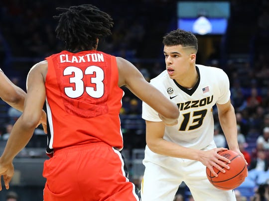 Missouri Tigers forward Michael Porter Jr. (13) handles the ball as he is defended by Georgia Bulldogs forward Nicolas Claxton (33) during the second half of the second round of the SEC Conference Tournament at Scottrade Center. Georgia won 62-60.