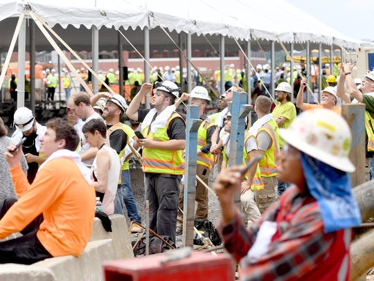 Construction workers watch as the final beams are hoisted