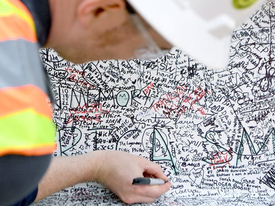 A construction worker finds a spot to sign his name on one of the two final beams of the Mission Hospital for Advanced Medicine before it is hoisted by crane to the top of the building in a topping off ceremony on Thursday, June 28, 2018. The beams were available for signatures at the hospital by patients, staff and members of the public who wanted to leave a mark on the new building.