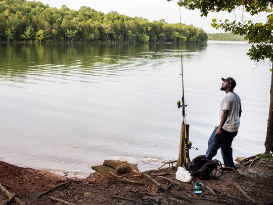 Blake Gant, of Nashville, fishes along the shore of