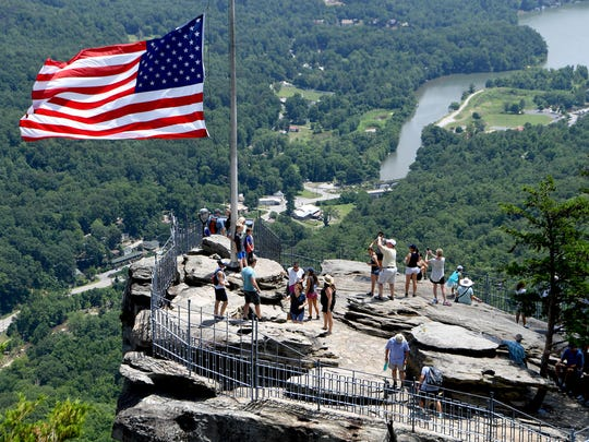 Visitors take in the view of Lake Lure from Chimney Rock at Chimney Rock State Park on Friday, June 29, 2018.