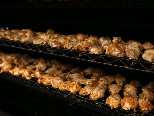 Anthony Sibona, owner of Hot Rods BBQ, lines the smoker