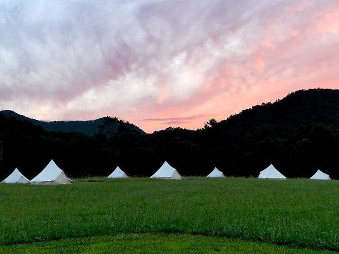 The sun sets over the Bell tents on platforms that