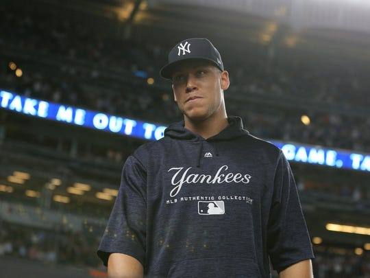 Jul 31, 2018; Bronx, NY, USA; New York Yankees injured right fielder Aaron Judge (99) stands on the field just outside the dugout during the seventh inning stretch of a game against the Baltimore Orioles at Yankee Stadium.