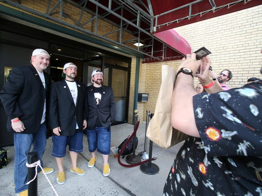 (center) Kevin Smith poses for a photograph with  Chris